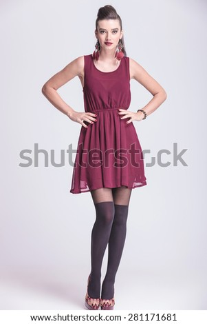 Full body picture of a elegant fashion woman posing with her hands around her waist. - stock photo