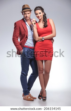 full body picture of a fashion couple posing in studio - stock photo