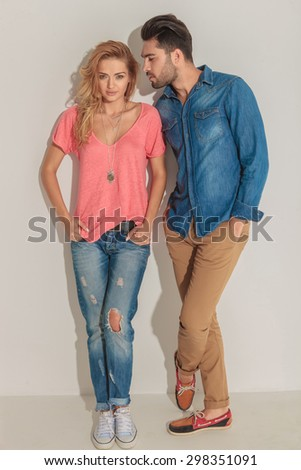 Full body picture of a gorgeous young woman leaning on a wall while her lover is looking at her. - stock photo