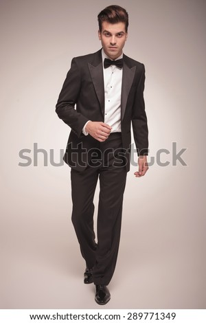 Full body picture of a handsome young business man walking on grey studio background, looking at the camera. - stock photo