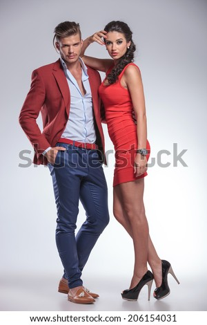 full body picture of a serious fashion couple posing in studio - stock photo