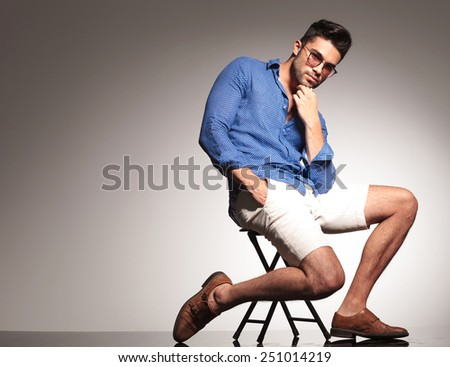 Full body picture of a smart casual young man holding one hand to his chin and the other one in his pocket while sitting on a stool. - stock photo