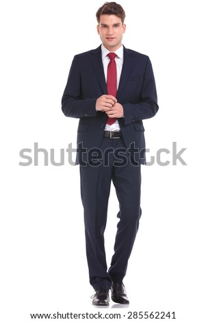 Full body picture of a young business man walking on isolated background. - stock photo