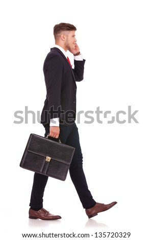 full body picture of a young business man walking to a side with his briefcase and speaking on the phone with a smile on his face. isolated on white background - stock photo