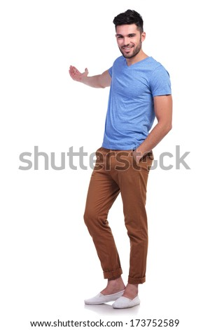 full body picture of a young casual man presenting something onwhite background - stock photo