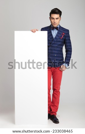 Full body picture of a young casual man showing a white empty board. - stock photo