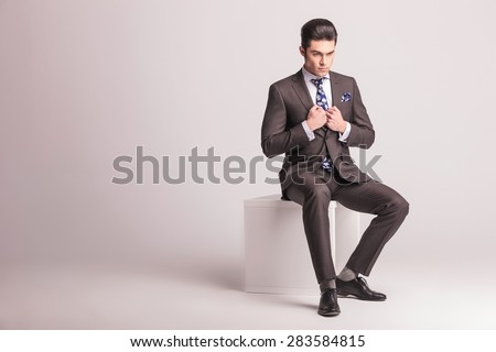 Full body picture of a young elegant business man sitting on a white chair while pulling his collar.