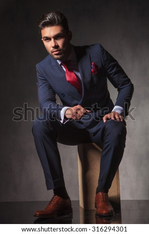 Full body picture of a young elegant business man sitting on a wood box while thinking. - stock photo