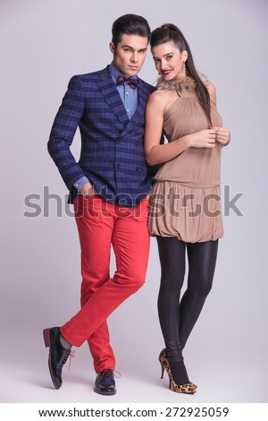 Full body picture of a young fashion couple posing together on grey studio background. - stock photo