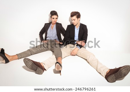 Full body picture of a young fashion couple relaxing on studio background with their legs apart. - stock photo