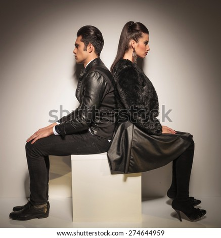 Full body picture of a young fashion couple sitting on a white table back to back, looking away from the camera.