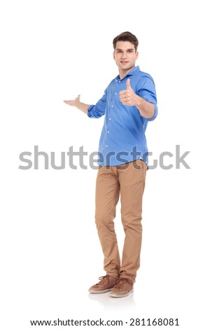 Full body picture of a young fashion man welcoming you while showing the thumbs up gesture. - stock photo