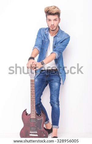 full body picture of a young guitarist holding down his electric guitar on white background - stock photo