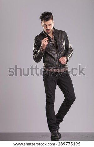 Full body picture of a young handsome man standing on studio background, touching his lips with a pair of sunglasses. - stock photo