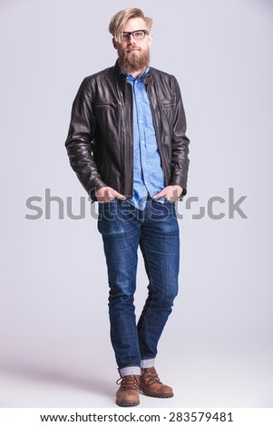 Full body picture of a young hipster man looking at the camera while holding his hands in pockets. - stock photo