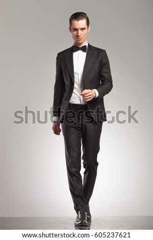 full body picture of a young man in tuxedo walking forward towards the camera on grey studio background