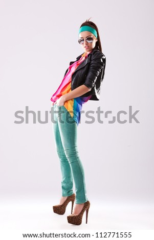full body picture of a young woman in high heels and leather jacket standing with her hands in pockets - stock photo