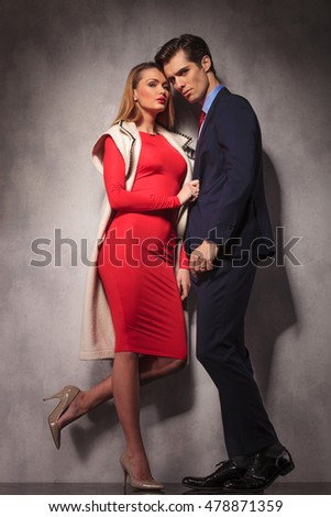 full body picture of an elegant couple , woman holding her lover by the coat, in studio