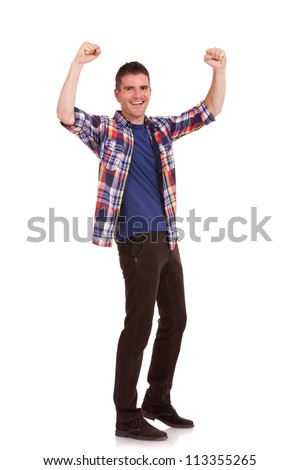 Full body picture of an excited casual young man cheering with his hands raised in the air, isolated on white background - stock photo