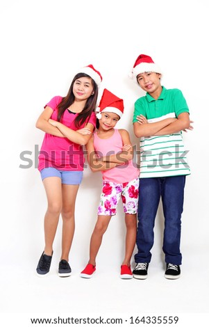 Full body picture of happy asian kids wearing Santa hat. - stock photo