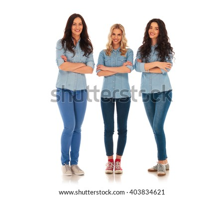 full body picture of three confident casual women standing on white studio background with hands crossed - stock photo