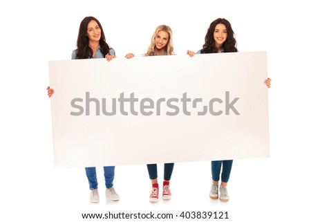 full body picture of three smiling casual women holding and showing a big blank billboard on white backogrund - stock photo