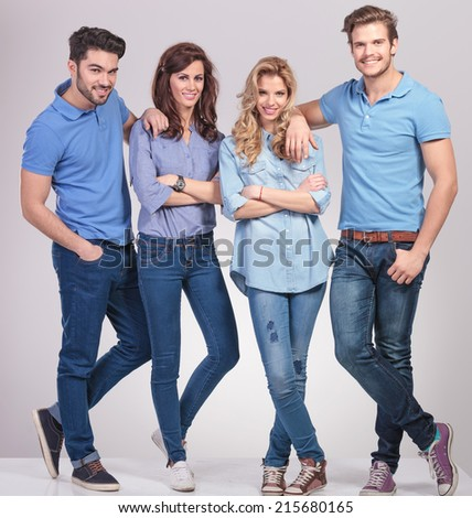 full body picture of young casual men leaning on women shoulders and smile on grey background - stock photo