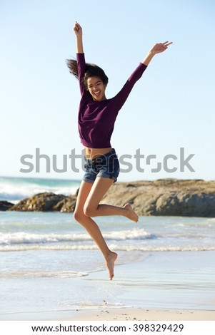 Full body portrait of a cheerful young black woman jumping by the beach - stock photo