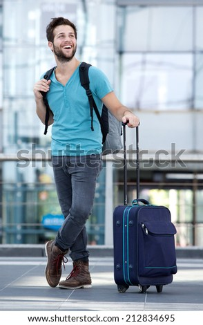 Full body portrait of a cool guy smiling with bags at airport