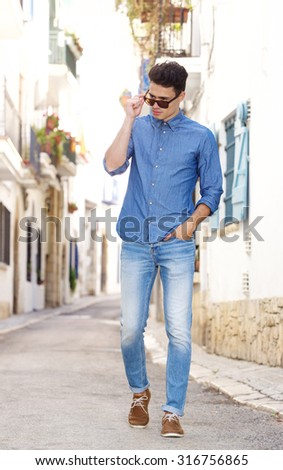 Full body portrait of a cool young guy walking on street in town - stock photo