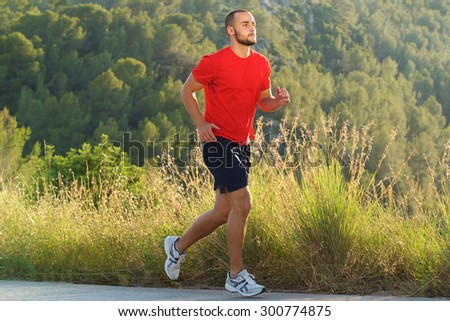 Full body portrait of a fit man running outdoors  - stock photo