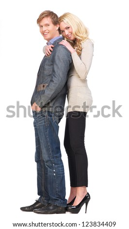 Full body portrait of a happy couple with a smile on their face. Beautiful girlfriend leans on her boyfriend's shoulder. Isolated on white background - stock photo