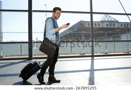 Full body portrait of a happy male traveler walking with bags and cellphone - stock photo