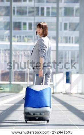 Full body portrait of a happy traveling business woman walking away with bag - stock photo
