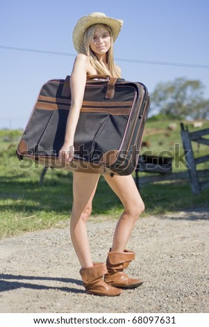 Full Body Portrait Of A Sexy Blond Female Tourist Holding Her Luggage In A Green Countryside Vacation - stock photo