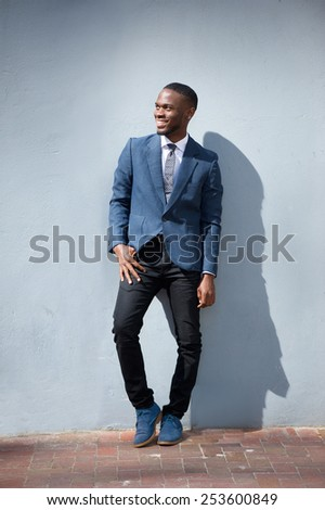 Full body portrait of a smiling business man standing against gray background - stock photo