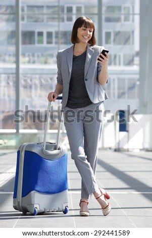 Full body portrait of a smiling business woman standing with mobile phone and bag at airport - stock photo
