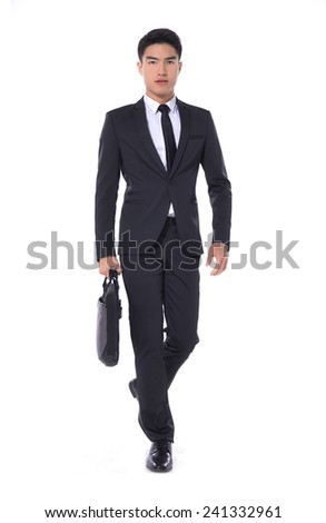 Full body Portrait of a successful young business man carrying a suitcase walking  - stock photo