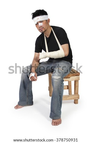 Full body portrait of an unhappy Asian man in bandage and gypsum sitting on a chair, isolated on white background - stock photo
