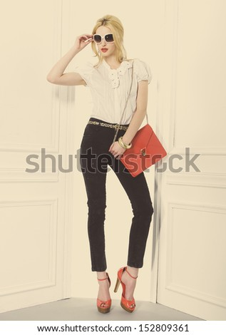 Full body Portrait of beautiful blonde girl holding red bag posing in studio - stock photo