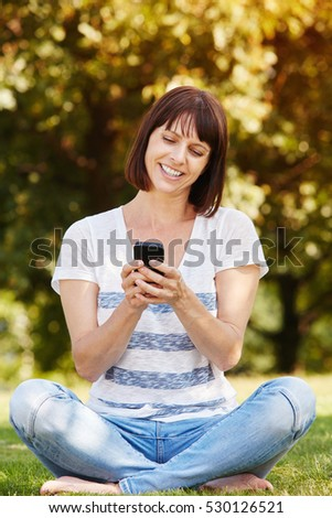 Full body portrait of beautiful older woman sitting in grass with smart phone