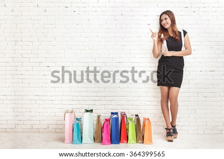 full body portrait of beautiful young woman standing next to shopping bags while pointing at copy space on white brick wall background - stock photo