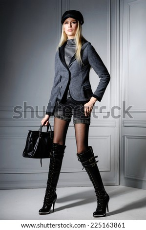 Full body portrait of fashion model with hat  holding bag posing in studio  - stock photo