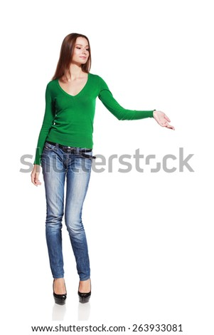 Full body portrait of happy smiling woman showing open hand palm with copy space for product or text - stock photo