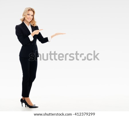 Full body portrait of happy smiling young businesswoman, showing something or blank copyspace area for slogan or text message, on grey background, with blank copyspace area for text or slogan - stock photo