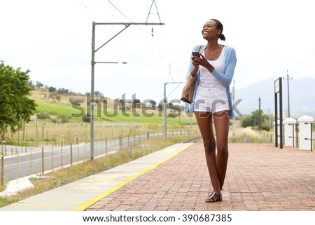 Full body portrait of happy young african woman at railway station with a mobile phone - stock photo