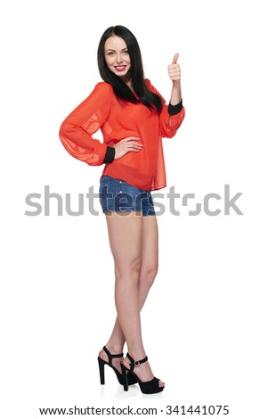Full body portrait of smiling fashion young woman in red top and denim shorts gesturing thumb up, isolated over white background - stock photo