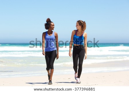 Full body portrait of two fit young women walking on beach - stock photo