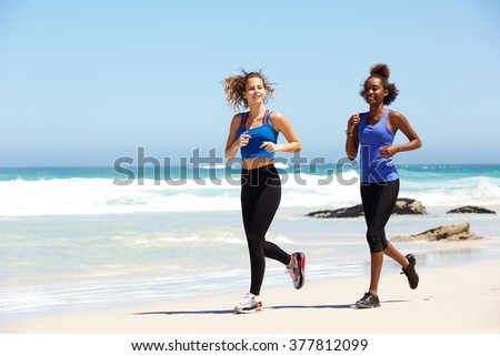 Full body portrait of two healthy young female runners at the beach