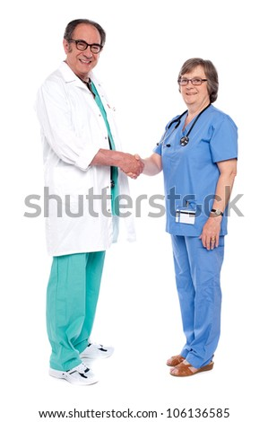 Full body portrait of two senior medical persons shaking hands isolated on white background - stock photo